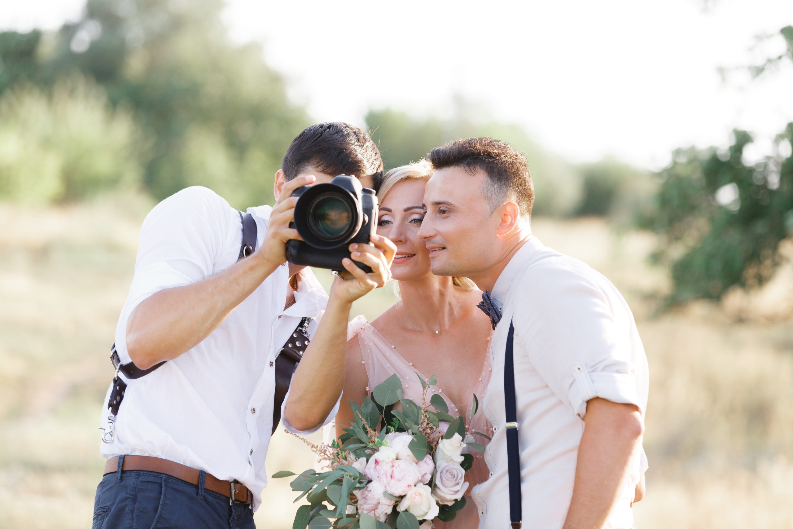 wedding photographer takes pictures of bride and groom in nature. photographer shows just taken photos to wedding couple