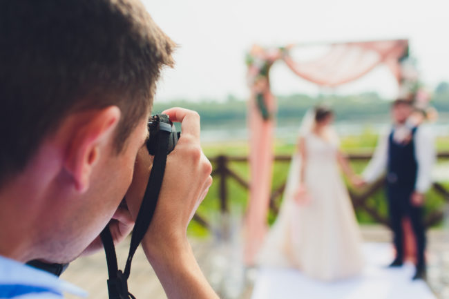wedding photographer takes pictures of bride and groom in city.